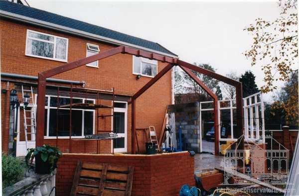 This steel spider has four legs bolted down onto steel footing pads with a steel central ridge beam around which the conservatory ridge shall be formed
